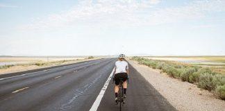 man cycling on a long road