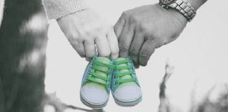 baby shoes held by mother's and father's hands